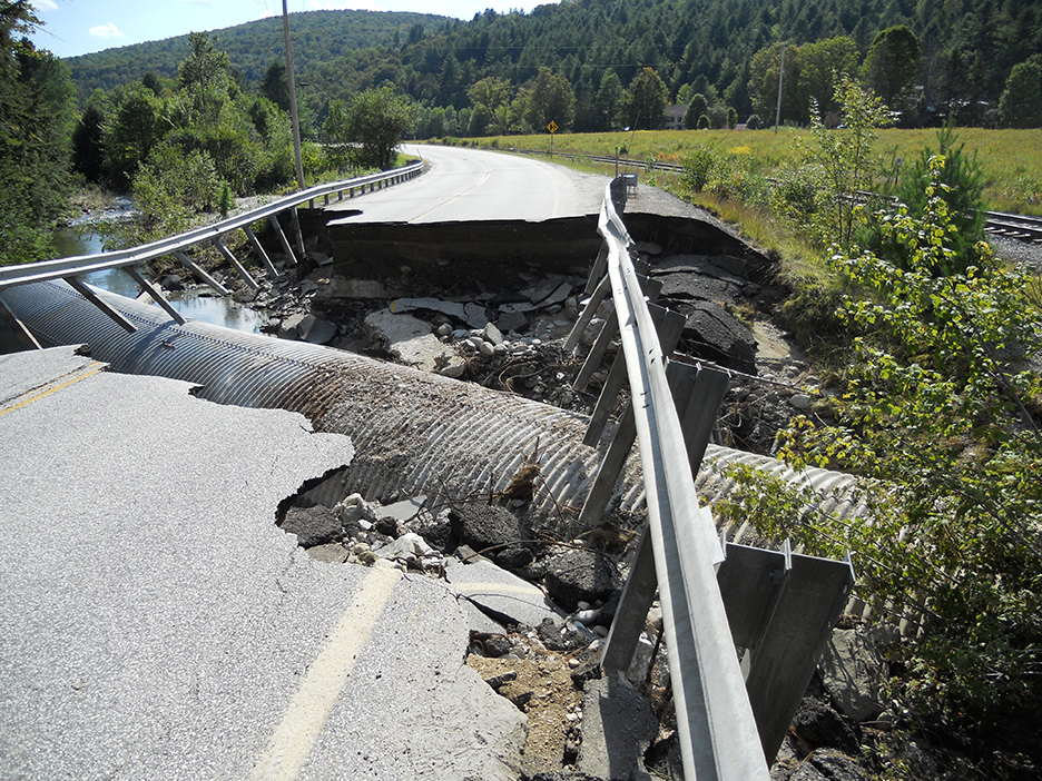 A picture of a collapsed road in a rural setting with pipes exposed underneath