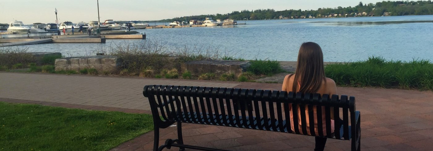 Woman sitting on a bench overlooking the Port Perry waterfront