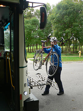 Loading a bike onto a bike rack on the front of a transit bus.