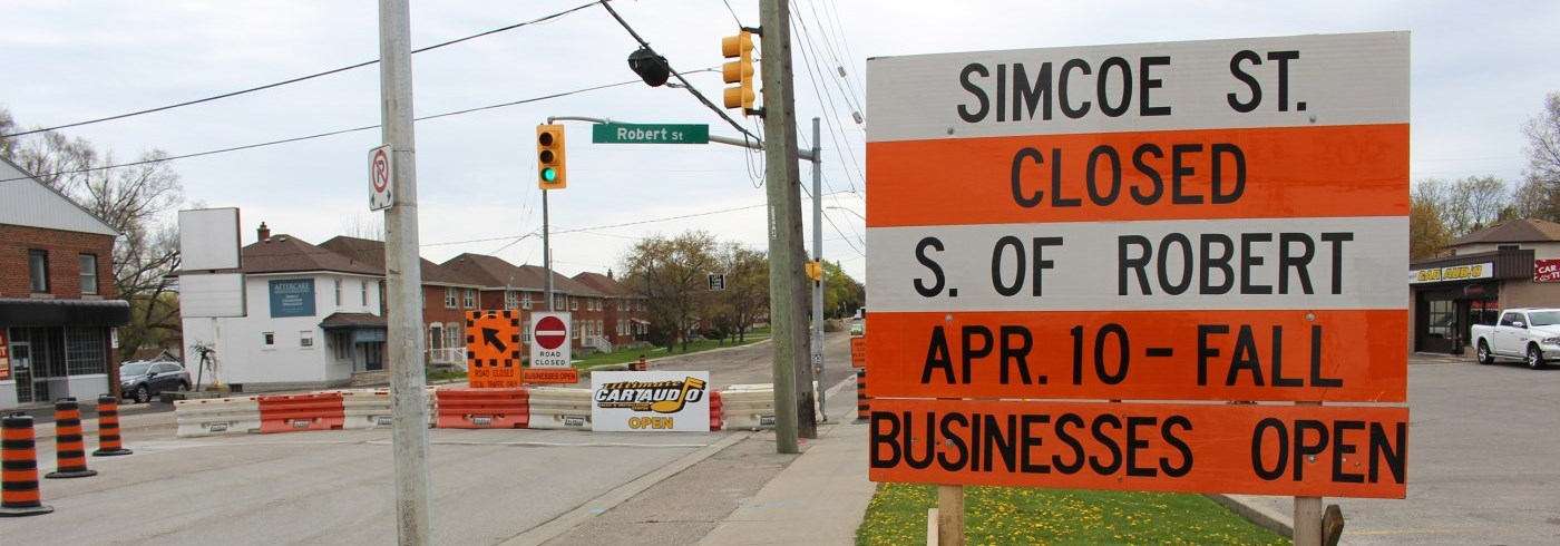 Simcoe Street road closure and businesses open sign