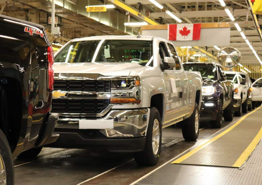 Trucks on a line inside the General Motors plant in Oshawa with a Canadian flag hanging in the background.