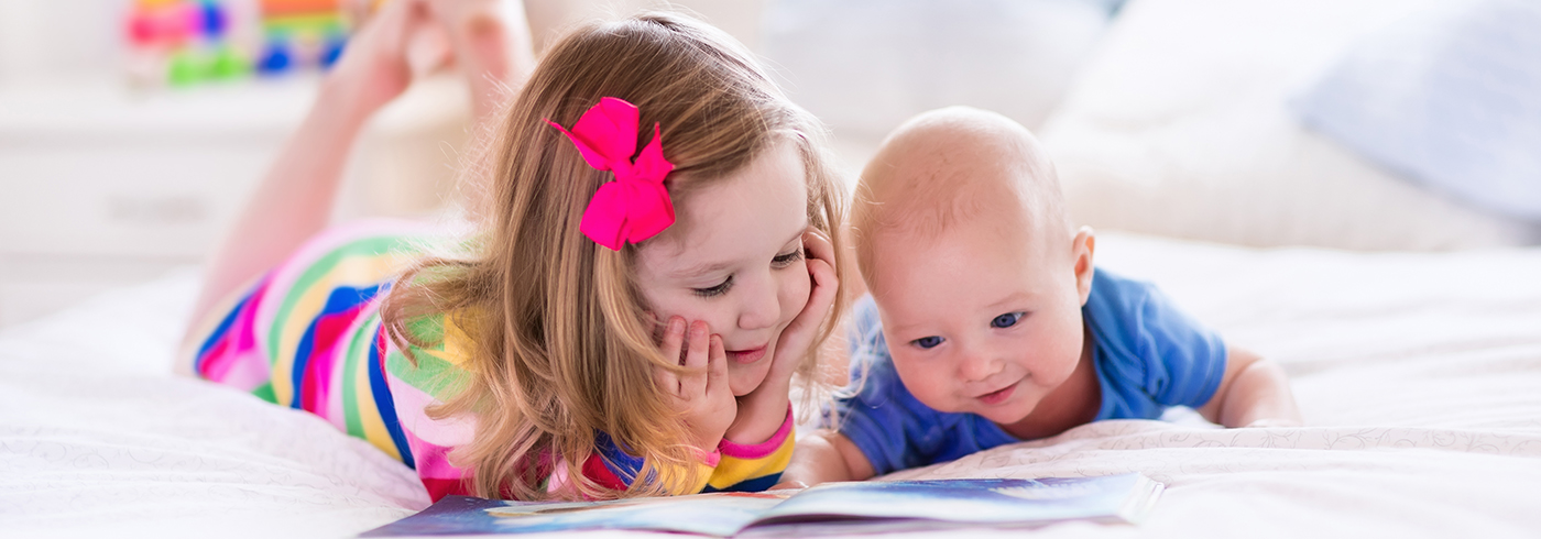 Toddler and baby looking at a book together