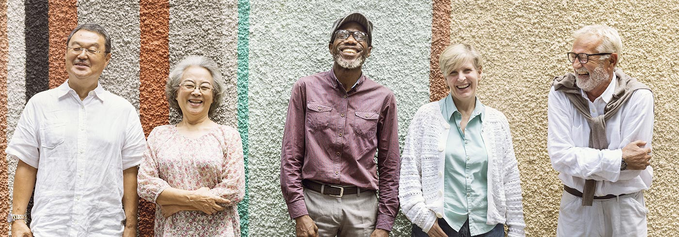 Group of older adults leaning against a wall.