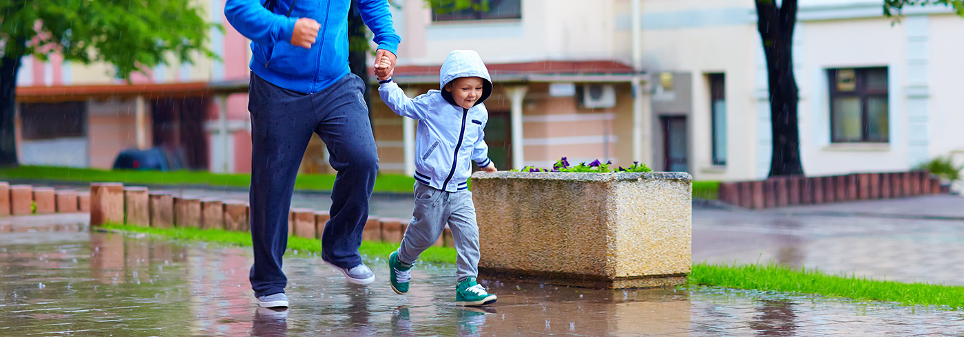 Dad and young son running in the rain.