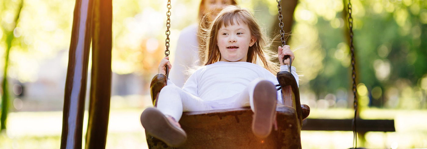 Young girl on playground swing.