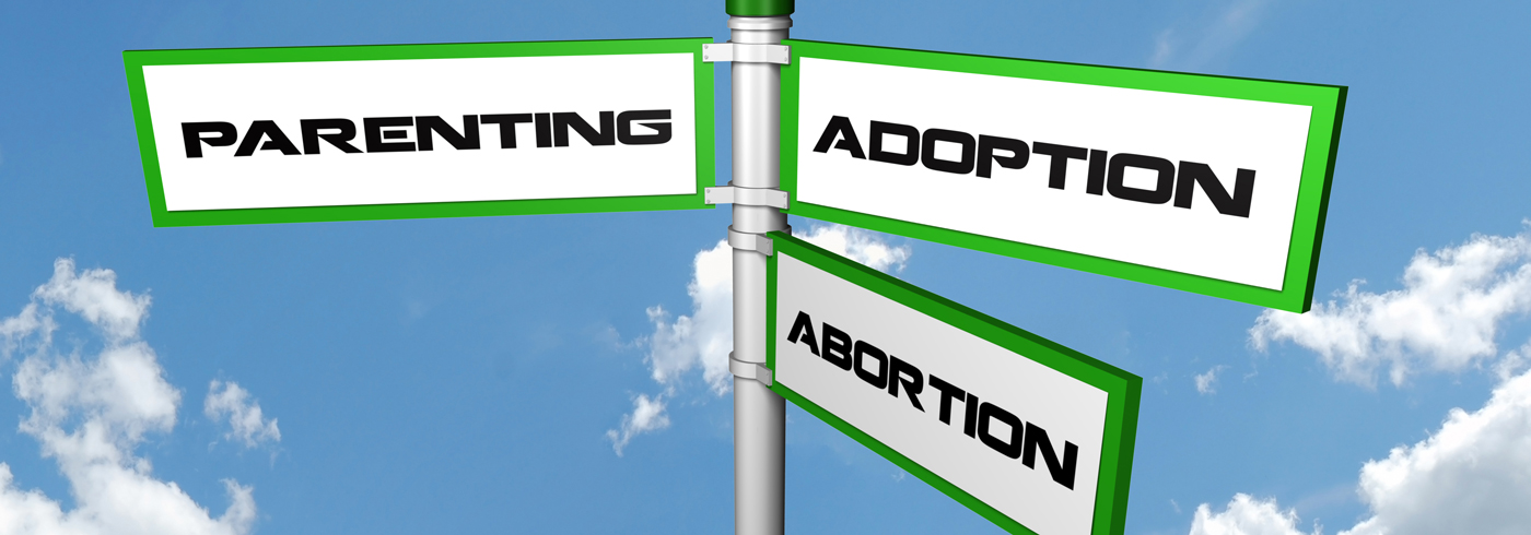 "Three signs stating ""parenting"", ""adoption"" and ""abortion""."