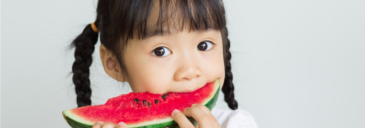Young girl eating a slice of watermelon.