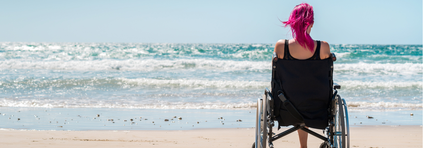 Woman in a wheelchair on the beach watching the ocean water.