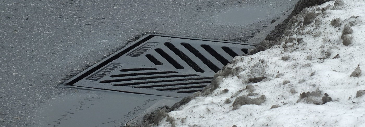 Storm sewer at side of road in winter