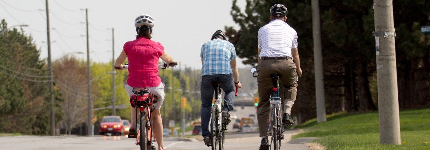Three people riding a bicycles on a sidewalk