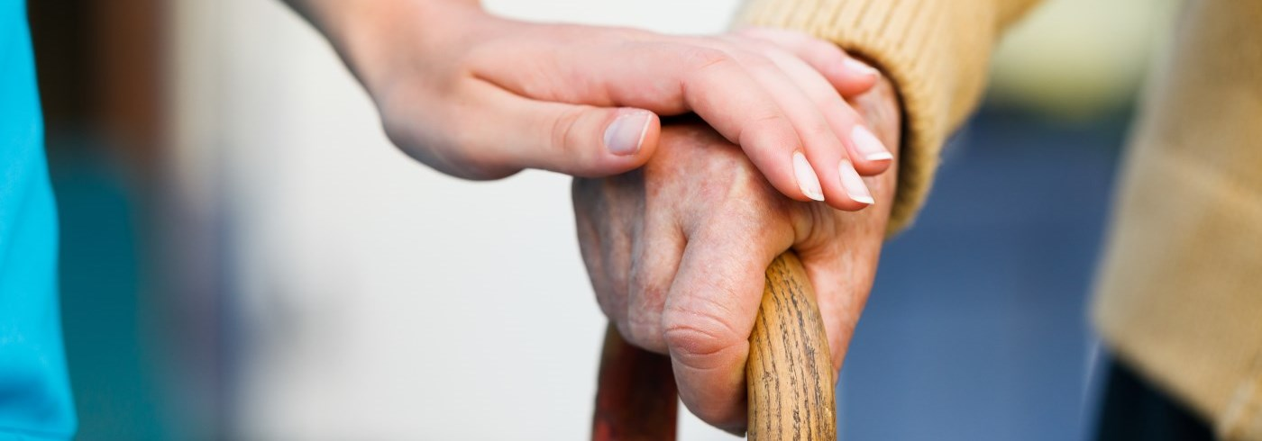 Woman's hand on elderly male's hand