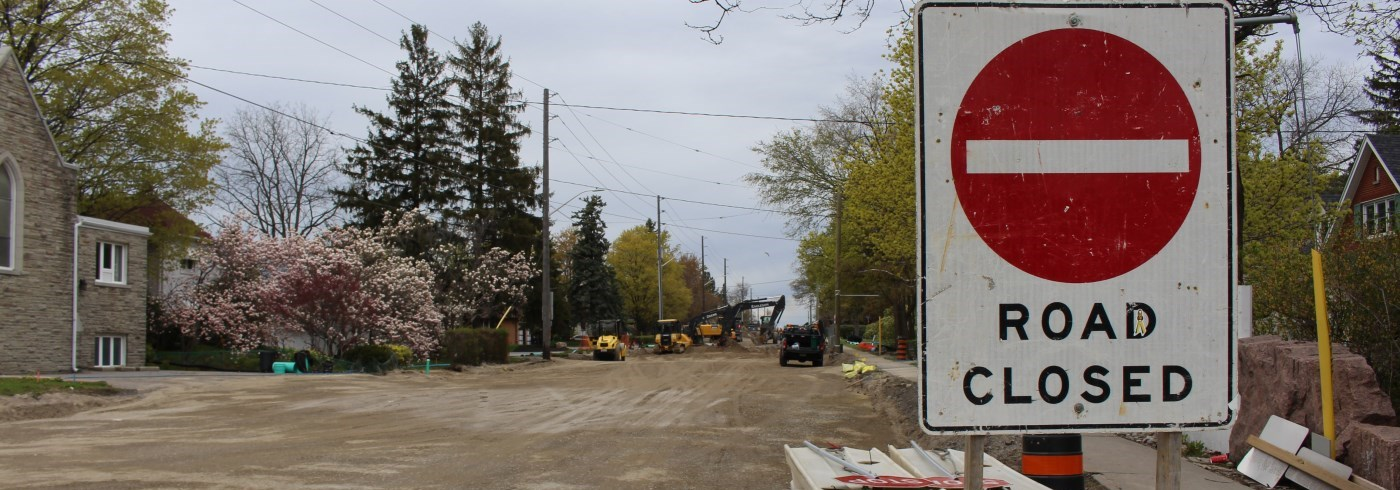 Road closure sign in front of construction vehicles performing road work