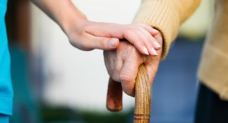 Woman's hand over man's hand holding cane