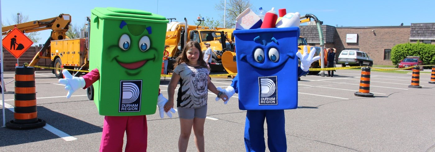 Young girl holding hands with green bin and blue box mascots at event
