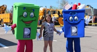 Waste management mascots with girl at event