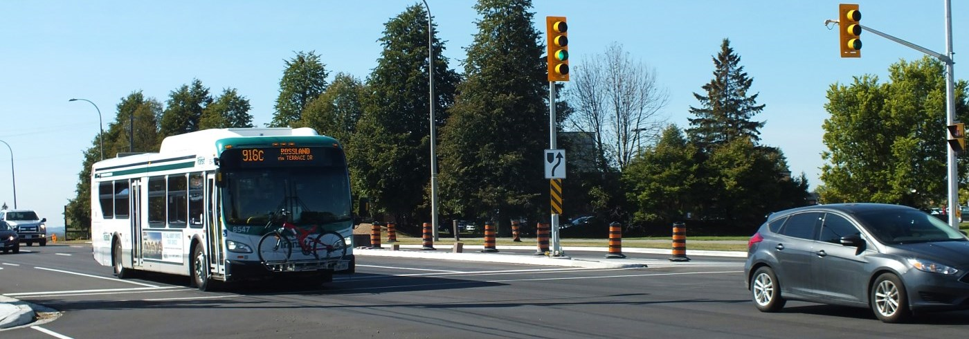 Car and Durham Region Transit bus, with bicycle on the front, driving through an intersection