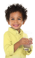 Boy with curly hair holding a glass of water