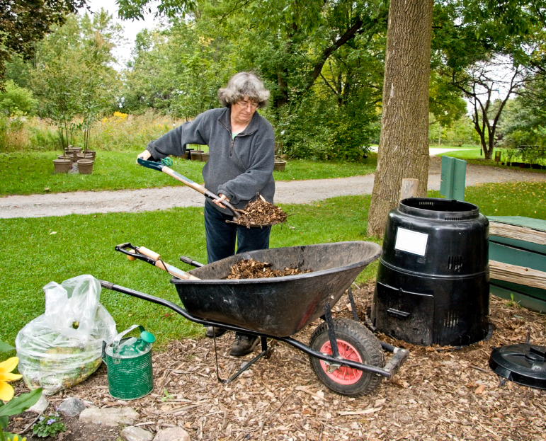 Women adding leaves to a backyard composter