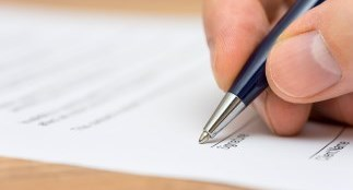Person using a pen to fill out an application