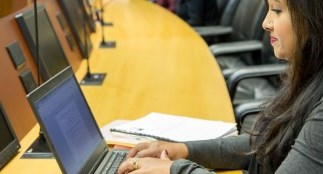 Woman typing on laptop in Council Chambers