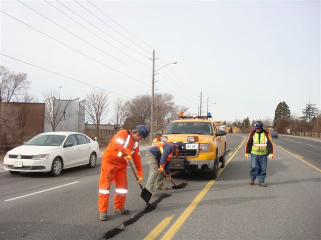Works Department staff fixing pothole in road