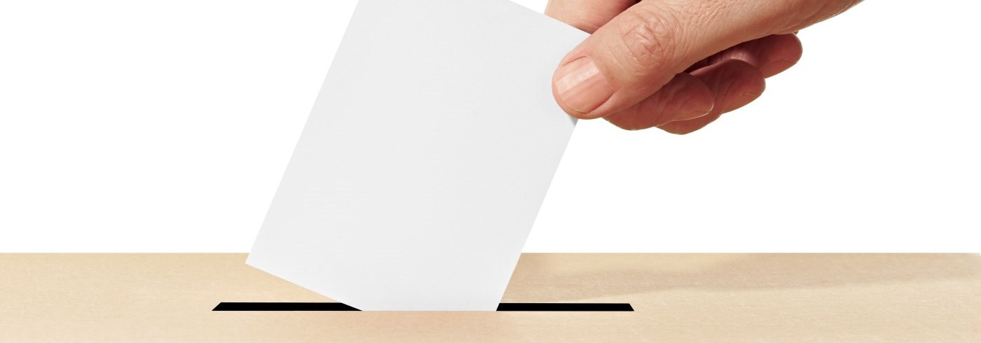 hand putting ballot into box