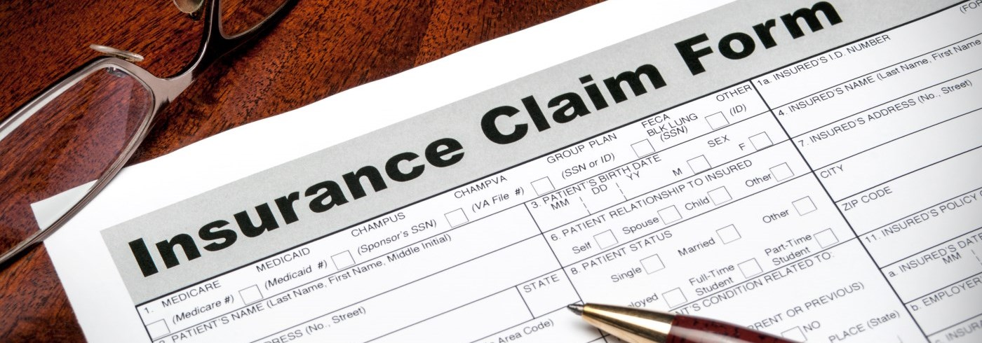 Insurance claim form with pen and eye glasses