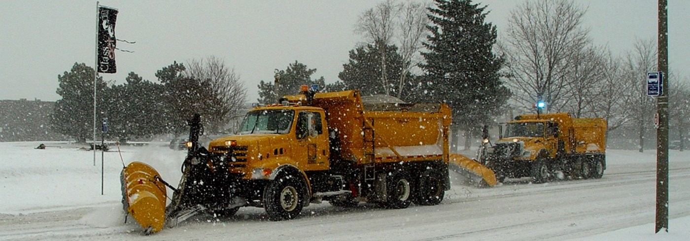Two yellow Region of Durham snow plows clearing snow off of a road