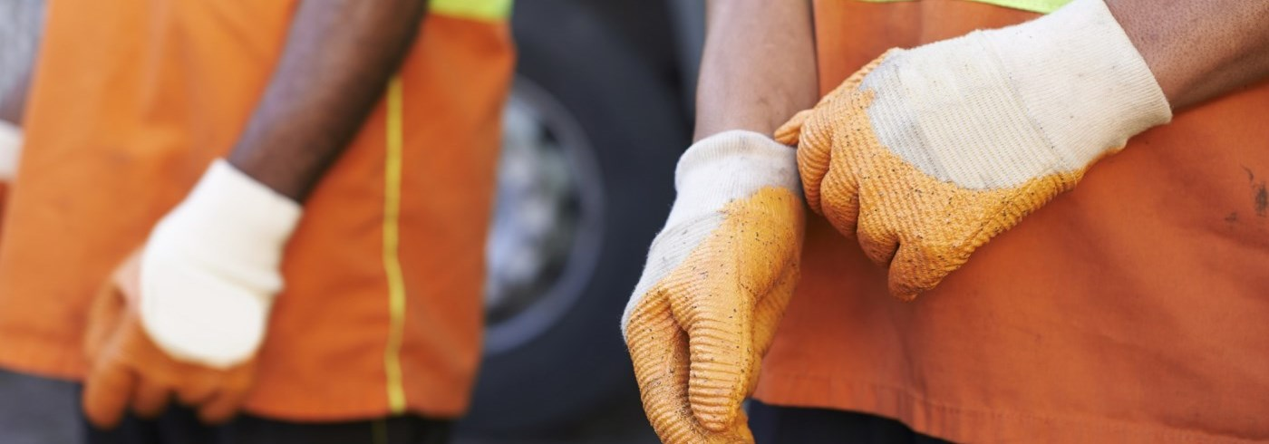 Two men wearing orange construction shirts and gloves