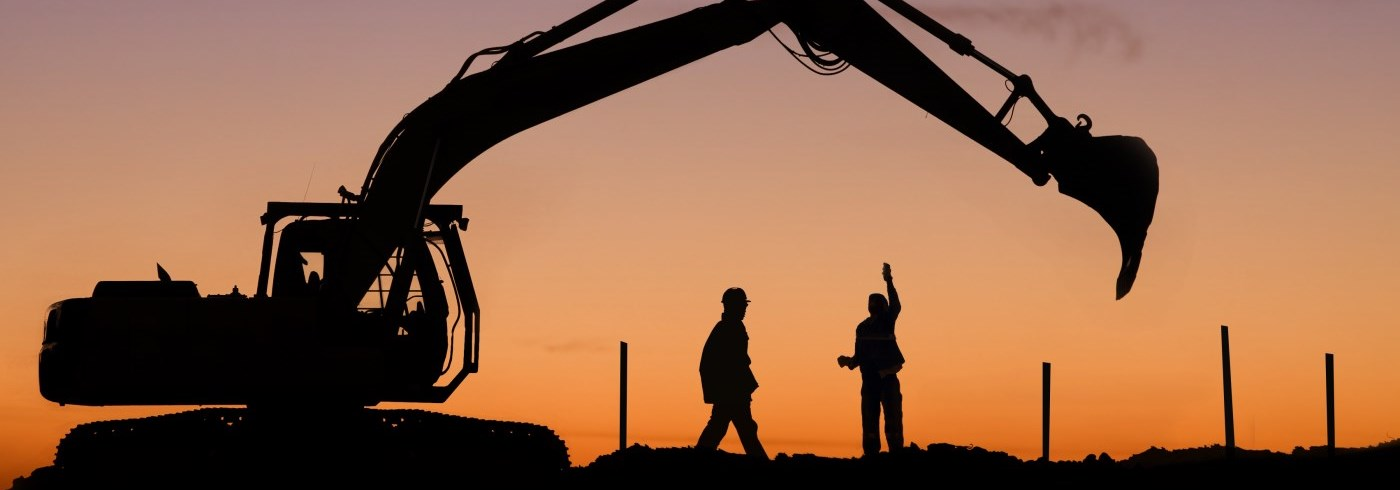 Two workers with machinery at sunset