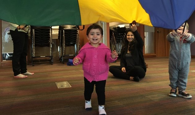 little girl playing under parachute with mom