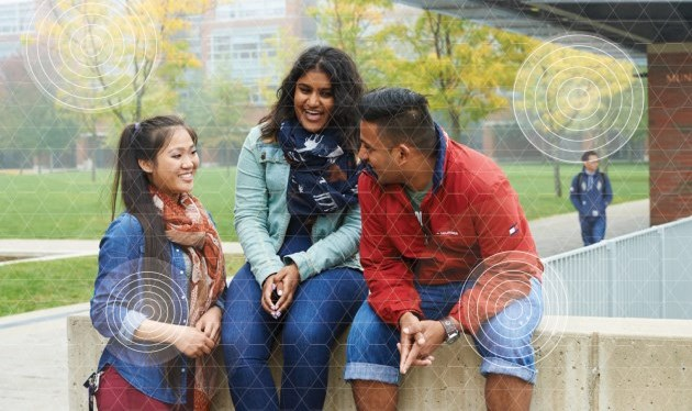 three university students talking outside a campus