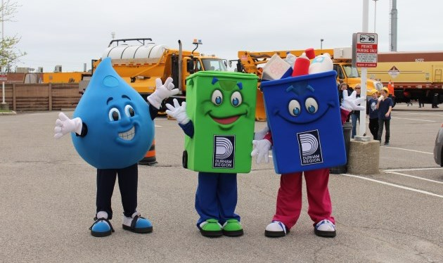 three waste themed mascots at an event